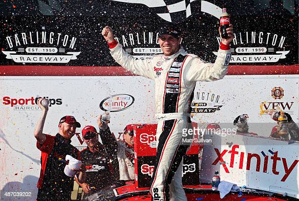 Denny Hamlin driver of the Sport Clips Toyota celebrates in Victory Lane after winning the NASCAR XFINITY Series VFW Sport Clips Help A Hero 200 at...
