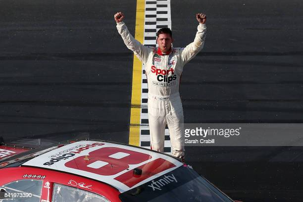Denny Hamlin driver of the Sport Clips Toyota celebrates winning the NASCAR XFINITY Series Sports Clips Haircuts VFW 200 at Darlington Raceway on...