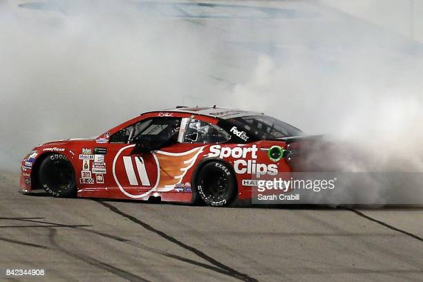 Denny Hamlin driver of the Sport Clips Toyota celebrates with a burnout after winning the Monster Energy NASCAR Cup Series Bojangles' Southern 500 at...