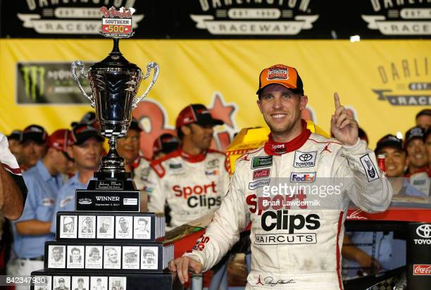 Denny Hamlin driver of the Sport Clips Toyota poses with the trophy in Victory Lane after winning the Monster Energy NASCAR Cup Series Bojangles'...