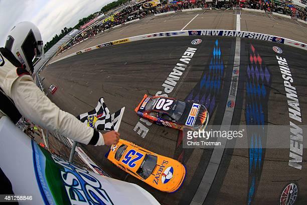 Denny Hamlin driver of the Sun Energy 1 Toyota takes the checkered flag to win the NASCAR XFINITY Series Lakes Region 200 at New Hampshire Motor...