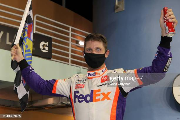 Denny Hamlin, driver of the Toyota, celebrates in Victory Lane after winning the NASCAR Cup Series Dixie Vodka 400 at Homestead-Miami Speedway on...