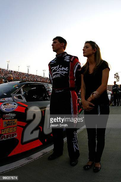 Denny Hamlin driver of the ZLine Designs / Operations Helmet Toyota looks on from the grid with girlfriend Jordan Fish during the performance of the...