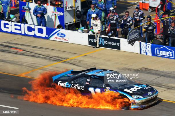 Denny Hamlin drives the FedEx Office Toyota on pit road as it bursts into flames after an incident during the NASCAR Sprint Cup Series Quicken Loans...