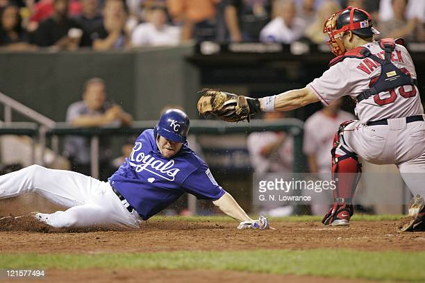 Denny Hocking of the Kansas City Royals slides in ahead of the tag by Jason Varitek of the Boston Red Sox at Kauffman Stadium in Kansas City Mo on...