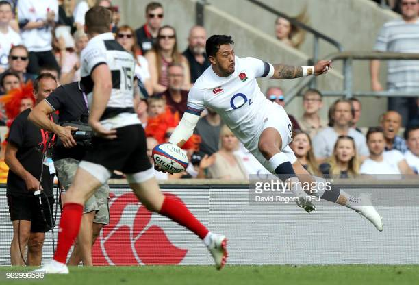 Denny Solomona of England offloads the ball during the Quilter Cup match between England and Barbarians at Twickenham Stadium on May 27 2018 in...