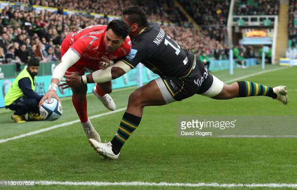 Denny Solomona of Sale Sharks dives in for a second half try despite being challenged by Taqele Naiyaravoro during the Gallagher Premiership Rugby...