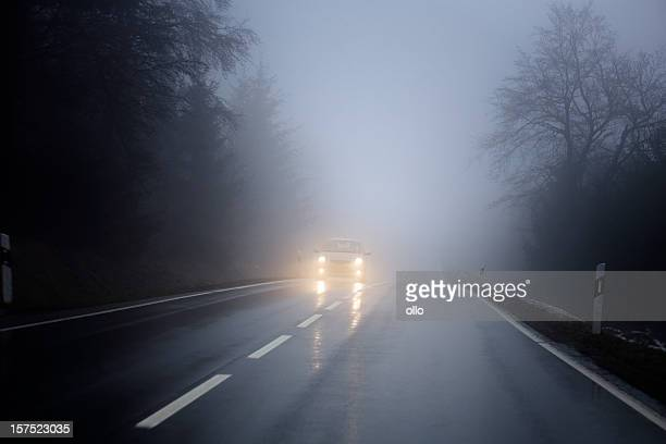 dense fog on the country road, oncoming traffic - fog stock pictures, royalty-free photos & images