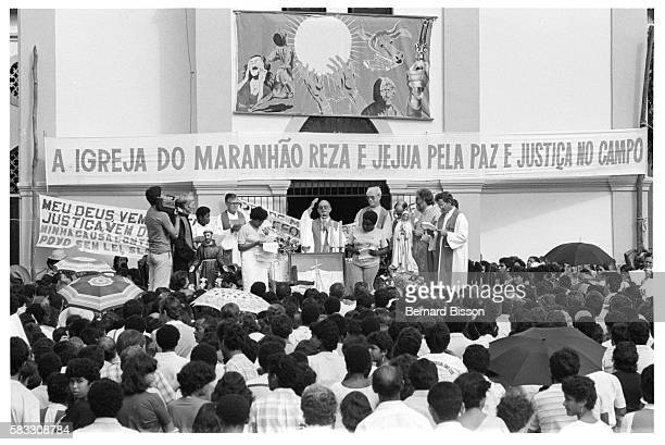 A densely packed crowd of followers attends a Liberation Theology service given from a raised platform outside a village church decorated with...