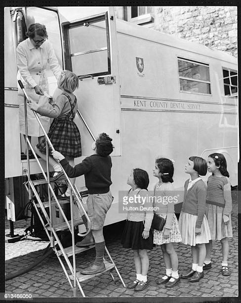 Dental assistant Mrs GA Hicks receives the school children as they climb the stairs to the mobile dental clinic where they will receive treatment in...