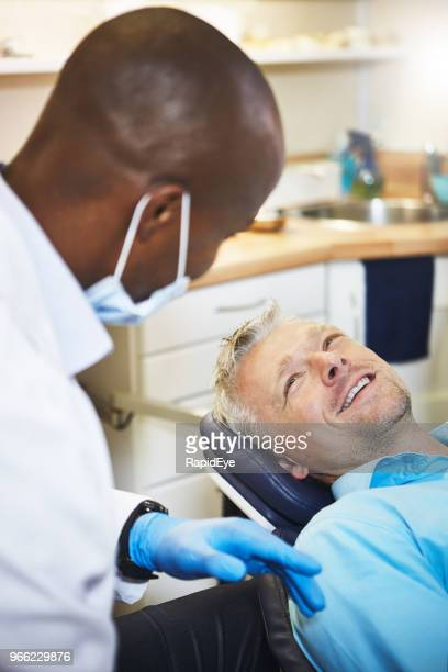 Dental check-up: smiling patient talks to dentist