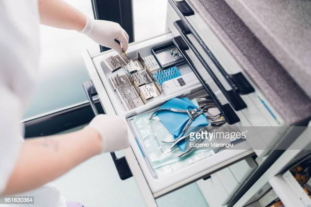 Dental nurse preparing dentistry equipment, close-up, elevated view