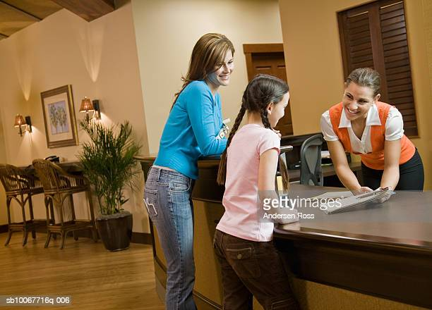 Dental receptionist explaining document to mother and daughter (10-11)