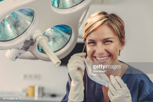 dental surgeon removing surgical mask, portrait - zahnarzt stock-fotos und bilder