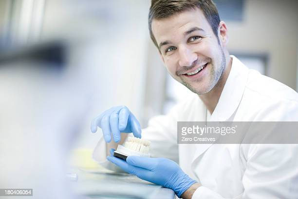 Dental technician holding denture