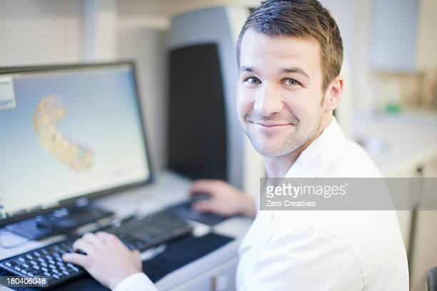 Dental technician using computer to design denture