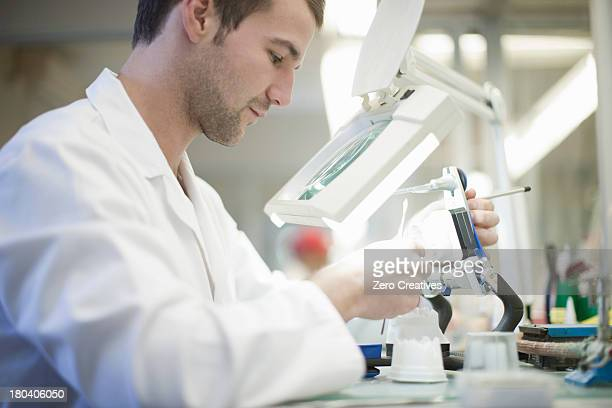 Dental technician using magnifier to repair denture