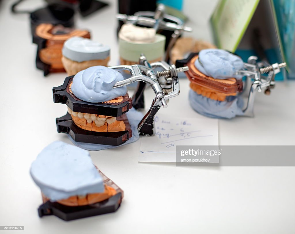 Dental technician working with articulator in dental laboratory : Stock Photo