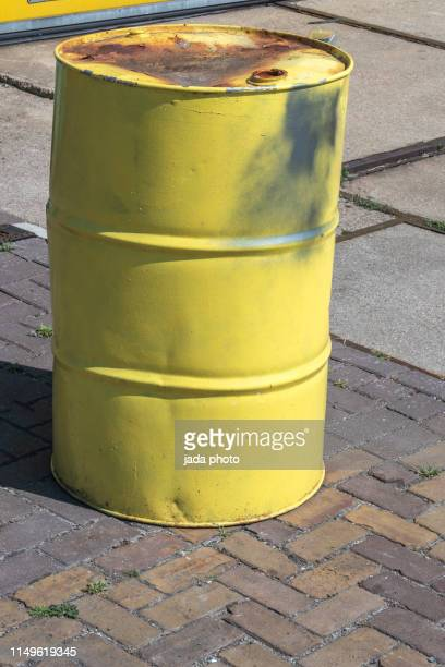 dented and rusty yellow colored oil barrel - stahlfass stock-fotos und bilder
