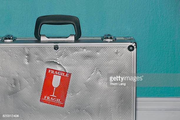 dented metal suitcase with fragile sticker - fragile sticker stock pictures, royalty-free photos & images