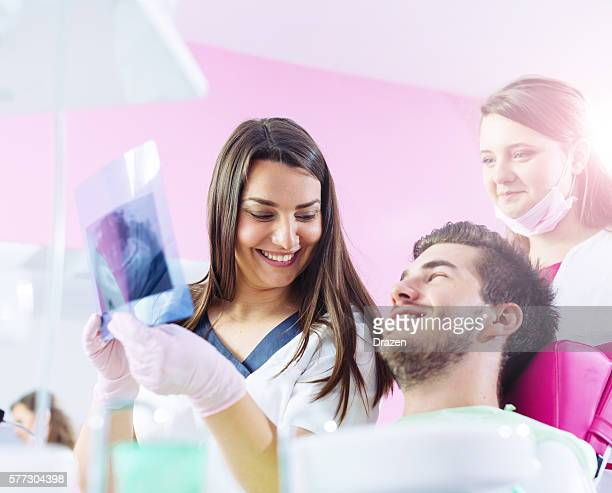 Dentist analyzing patient's x-ray and smiling