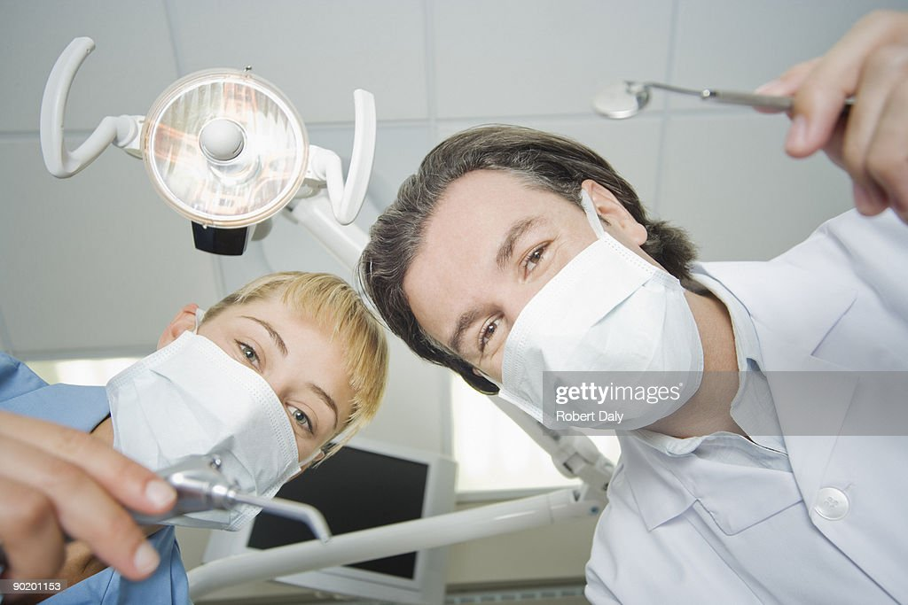 Dentist and assistant leaning down to work on patient : Stock Photo