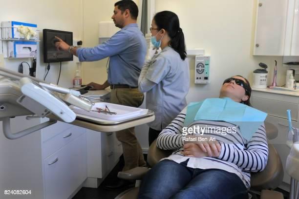dentist and dental assistance examining teeth of a patient - rafael ben ari stock-fotos und bilder