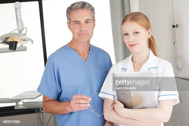 Zahnarzt und dental assistant im Prüfungsraum holding Diagrammen und Lächeln