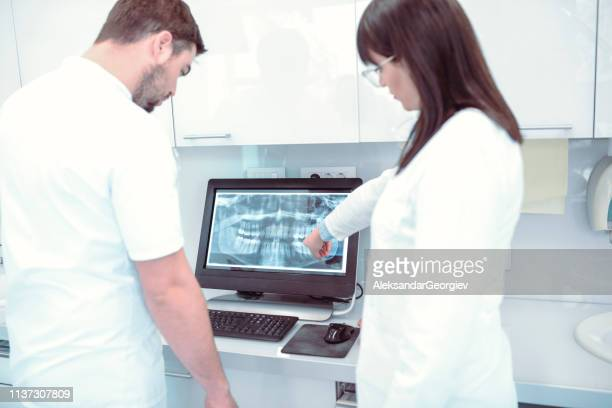 Dentist And His Assistant Analyzing Dental Scan