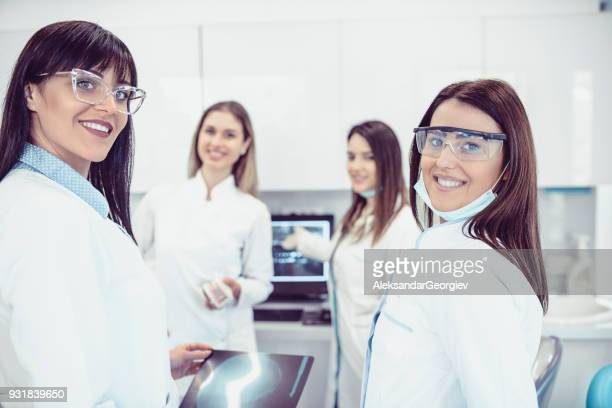 Dentist and Medical Team Examining Patient's X-ray Image and Posing in Dental Clinic