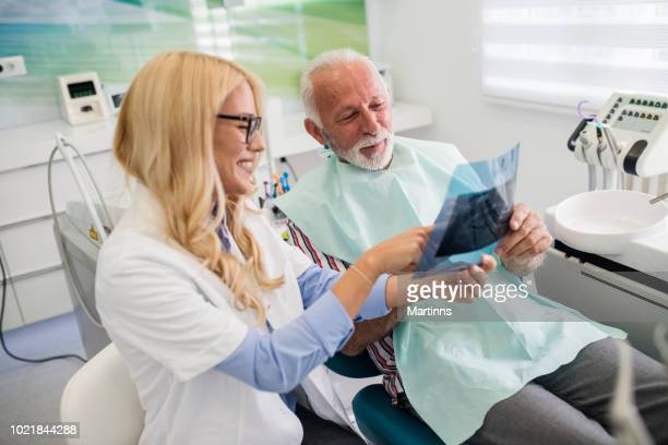 Dentist and patient looking at x-ray of teeth in a dentist`s office