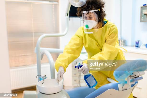 zahnarzthelferin mit starkem desinfektionsmittel zur reinigung der zahnarztpraxis für den nächsten patienten - kopfbedeckung stock-fotos und bilder