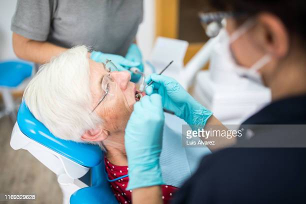 dentist checking teeth of elderly female in clinic - partie du corps humain photos et images de collection