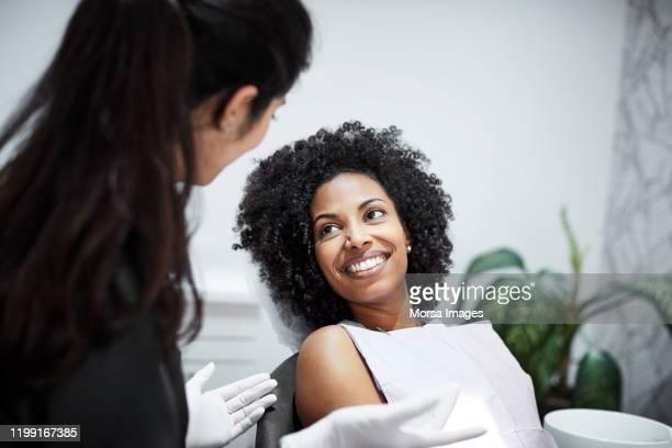 zahnarzt diskutiert mit lächelnder patientin - zahnpflege stock-fotos und bilder