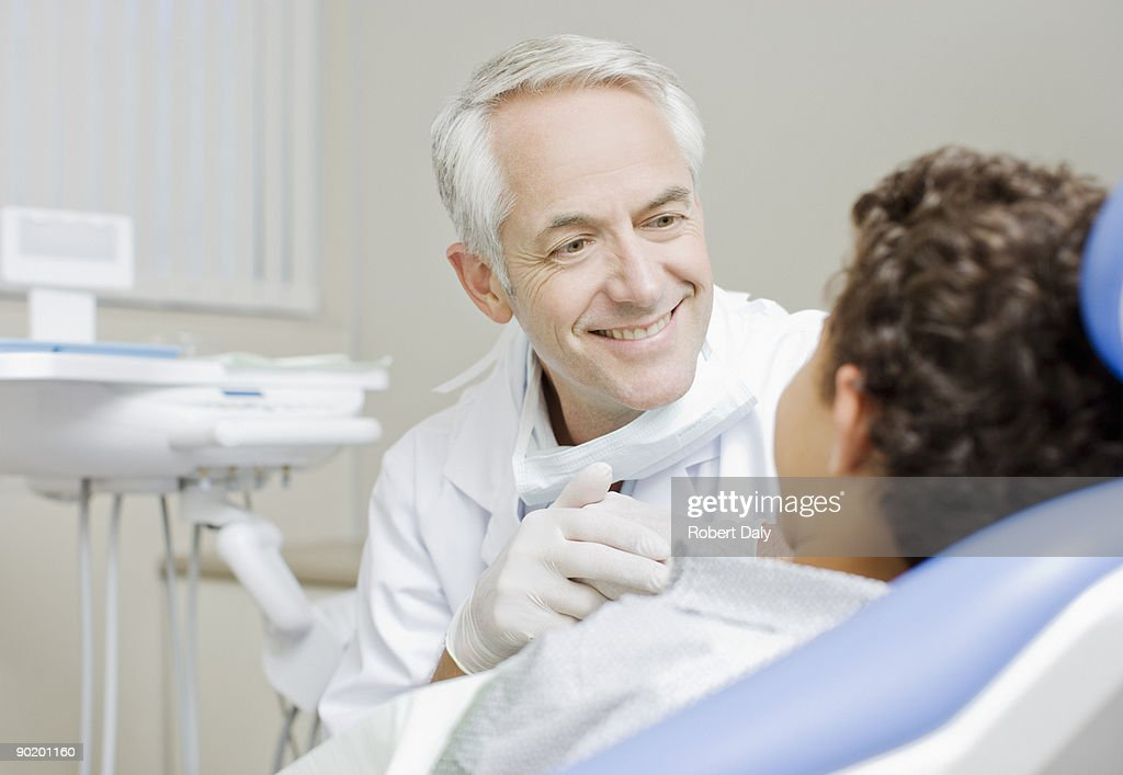 Dentist examining boys teeth : Stock Photo
