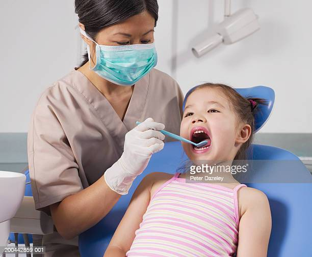 dentist examining girl's (4-6) teeth - pediatric dentistry stock photos and pictures