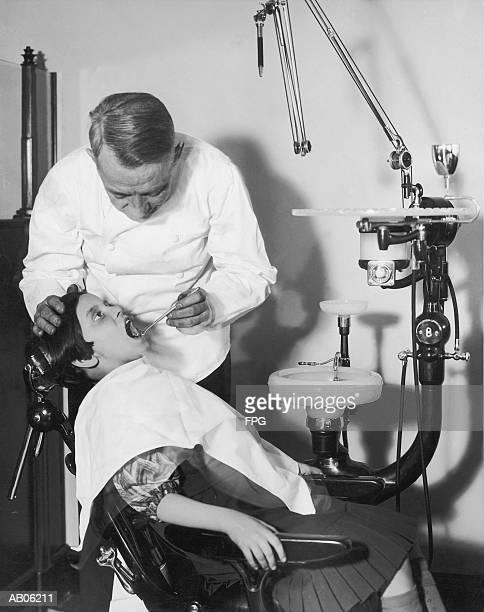 dentist examining girl's (8-10) teeth (b&w) - dentist 1950 stockfoto's en -beelden