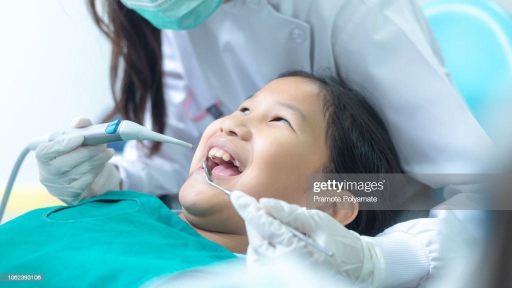 Dentist examining little girl's teeth in clinic. : Stock Photo