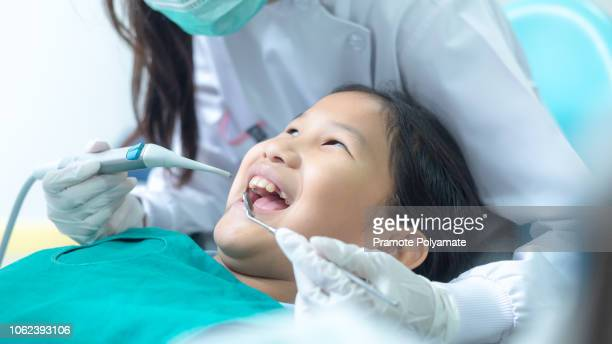 Dentist examining little girl's teeth in clinic.