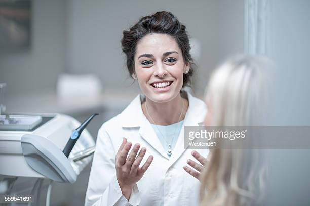 Dentist explaining procedure to patient sitting in dentists chair