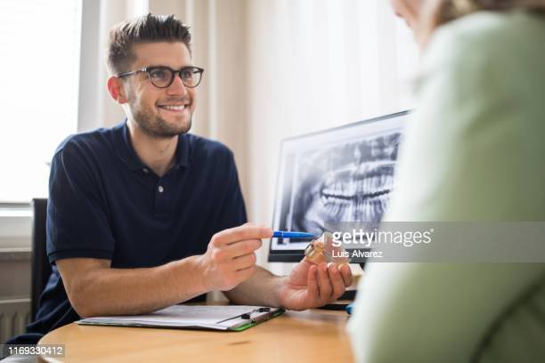 dentist explaining the dental treatment to patient - medical procedure stock pictures, royalty-free photos & images