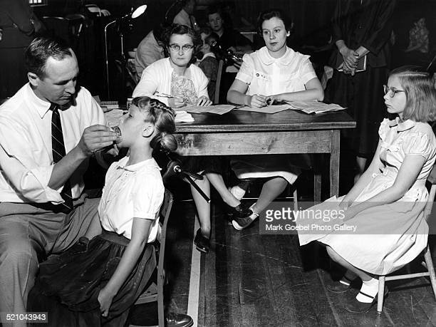 Dentist giving exam to grade school girl late 1950s or early 1960s