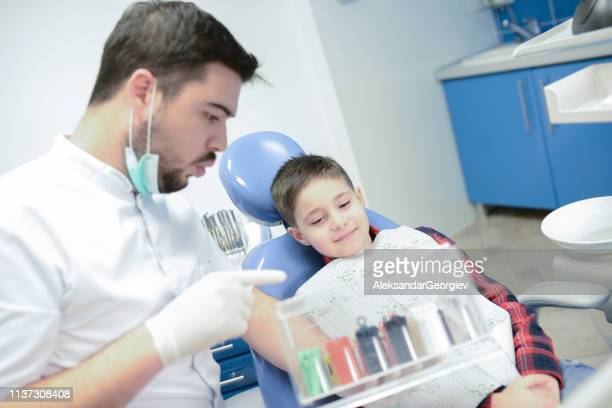 Dentist Helping Boy Choose Braces Color