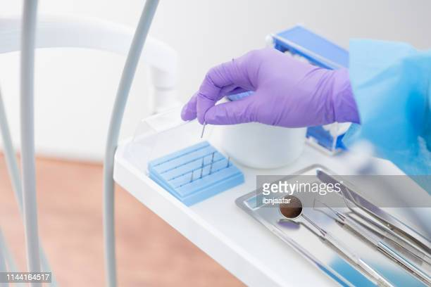 dentist holding dental burs - purple glove stock pictures, royalty-free photos & images