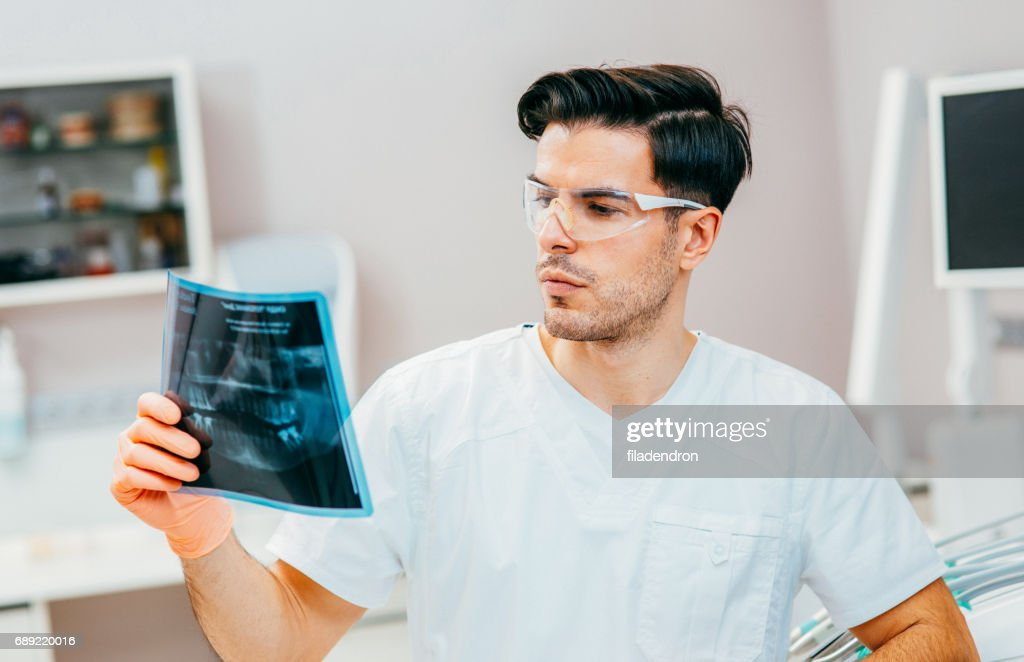 Dentist looking at an x-ray : Stock Photo