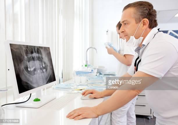 dentist looking at x-ray image