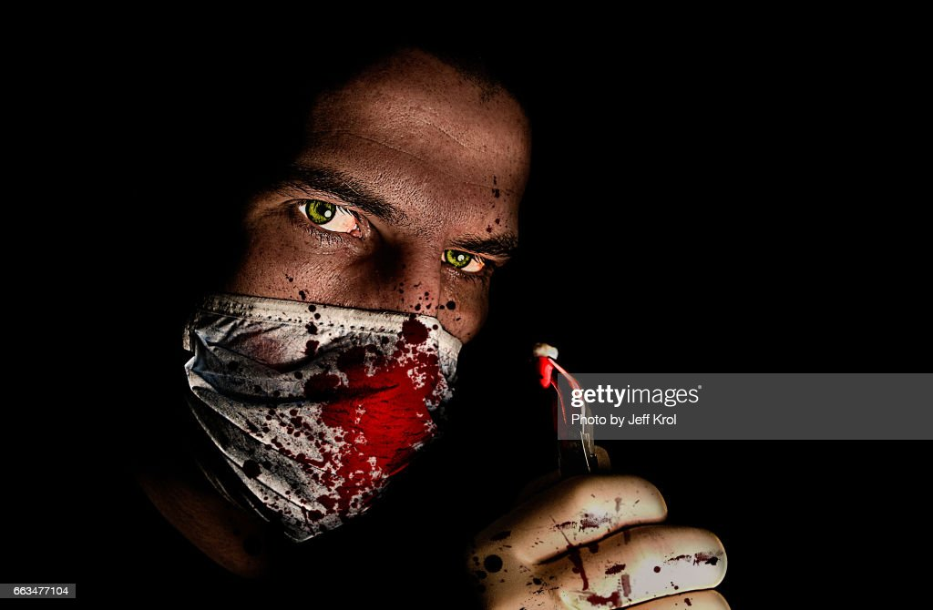 Dentist looking man, wearing bloody dust mask, holding a tooth in his hand with : Stock Photo