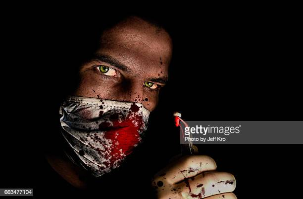 dentist looking man, wearing bloody dust mask, holding a tooth in his hand with - tekstveld stock pictures, royalty-free photos & images