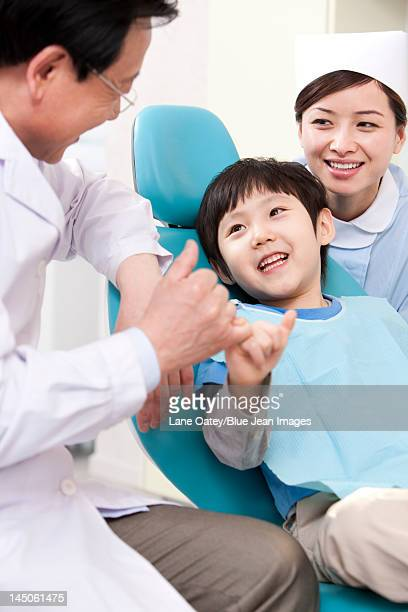 Dentist making promise with a little patient