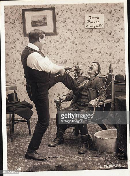 A 'dentist' pulls a giant tooth from another man who is chained to a chair in front of a sign which reads 'Teeth pulled while you wait' 1905 Photo by...